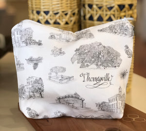 Pictured is a medium sized black and white Toile of Thomasville pouch.