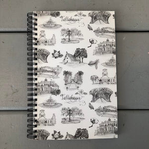 There is a small spiral bound notebook with a black and white Toile of Tallahassee cover.