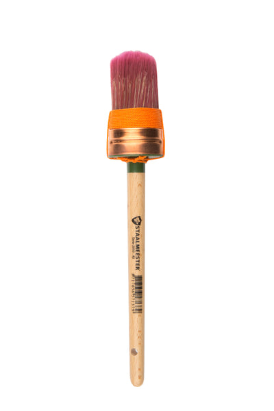 Pictured is a staalmeester paintbrush with a small oval-shaped tip. The bristles are red and there is orange string wrapped around their base. The handle is long and natural wood, except for just below the bristles where the handle is green.