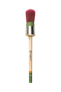 Pictured is a staalmeester paintbrush with a round brush tip. The bristles are red and the string wrapped around the based of the bristles is green. It has a long, natural wood handle with a green tip.
