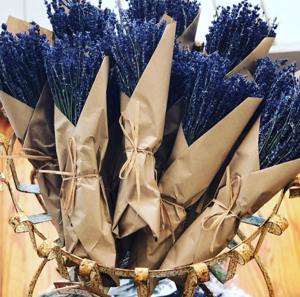 Pictured are several bundles of French lavender. They are wrapped in crisp brown paper and tied with twine.