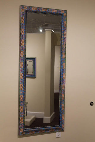 A full length mirror is pictured. The frame is painted ornately in bright colors.