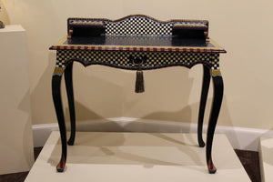 Pictured is an ornately painted desk. Its legs are curved outward and are painted black. The body of the desk is painted in a checkered pattern with multi-color designs on the borders.