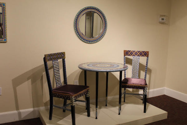 Pictured is a bistro dining set. There are two chairs and one small table between them. All of them are painted ornately in geometric patterns.