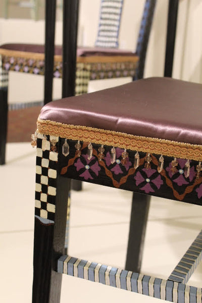 Pictured is a detail from the dining chair. The background paint is black. There are several different designs including stripes, checkered, and a floral design. The cushion of the chair is upholstered with a burgundy leather-like fabric. It is bordered with a textured gold ribbon.