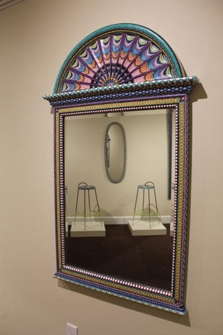 Pictured is a rectangular mirror. It has a semicircular fan like design on top. The wooden frame and fan are both painted ornately in brightly colored patterns.