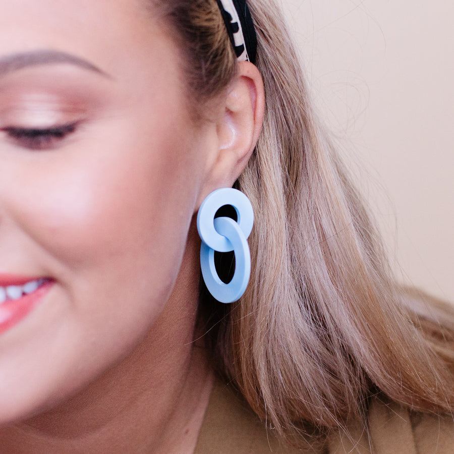A pair of periwinkle, flat-edged hooped earrings