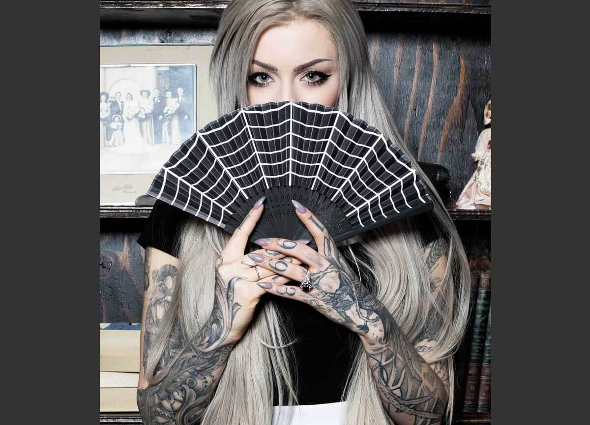 Image of tattooed model holding spiderweb fan