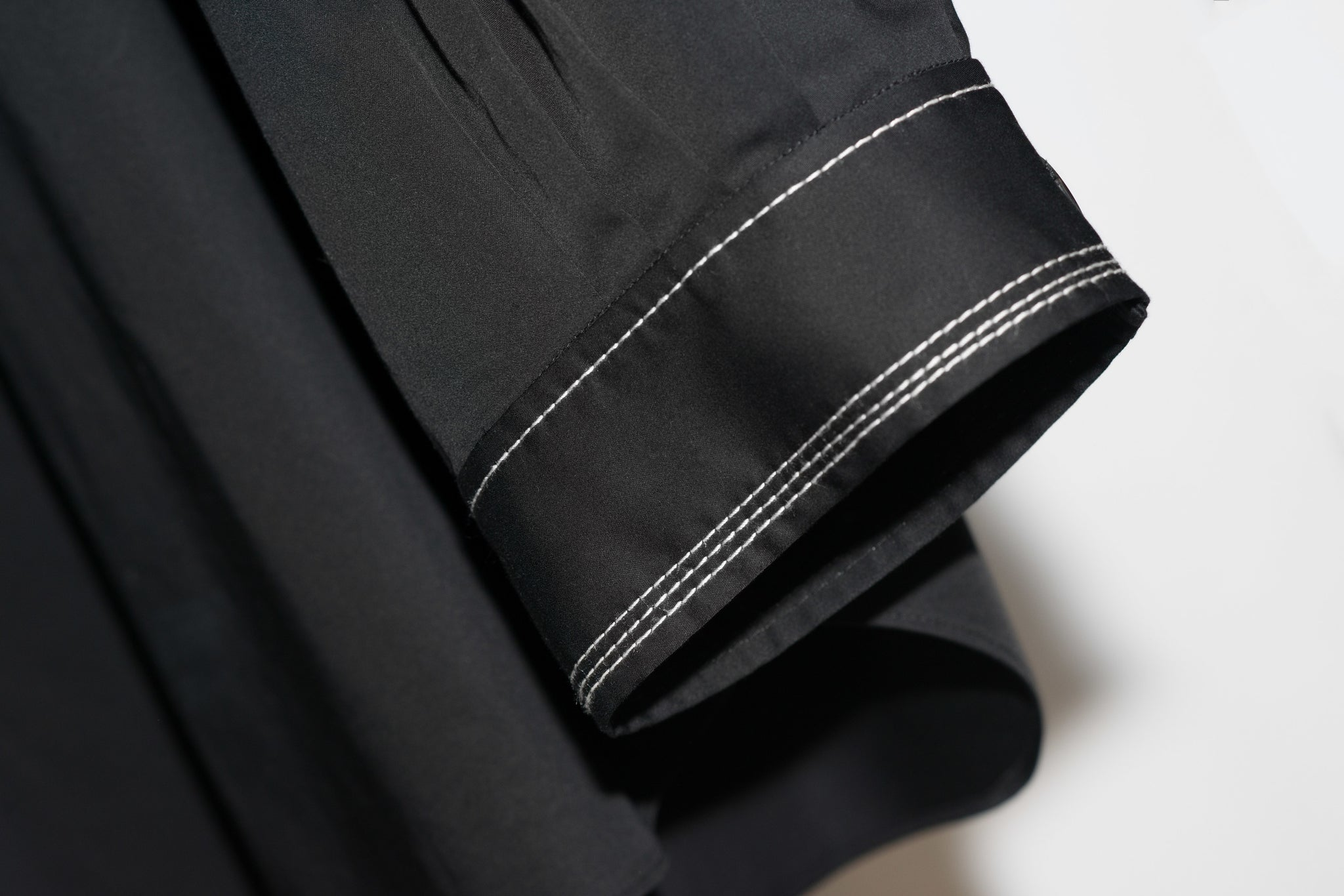 balloon-sleeve black top with white-stitched cuffs