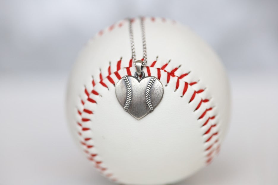 Baseball Heart Pendant in Sterling Silver Show your love of baseball with our Baseball Heart Pendant!  Product Details  Sterling silver Sterling silver cable chain Lobster clasp Pendant: 22mm Necklace box included