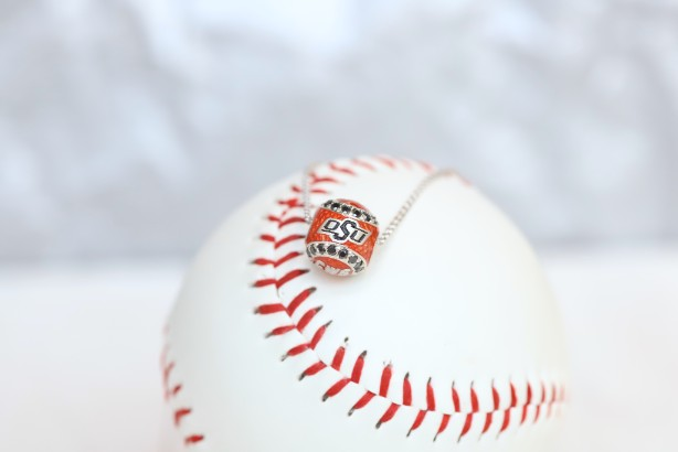 Show your support for Oklahoma State Cowboys orange and black diamond College World Series Baseball  with our officially licensed jewelry!  Product Details  Sterling silver Pendant: 12 mm Sterling silver cable chain with lobster clasp Features Orange enamel Black Diamonds Pendant box included