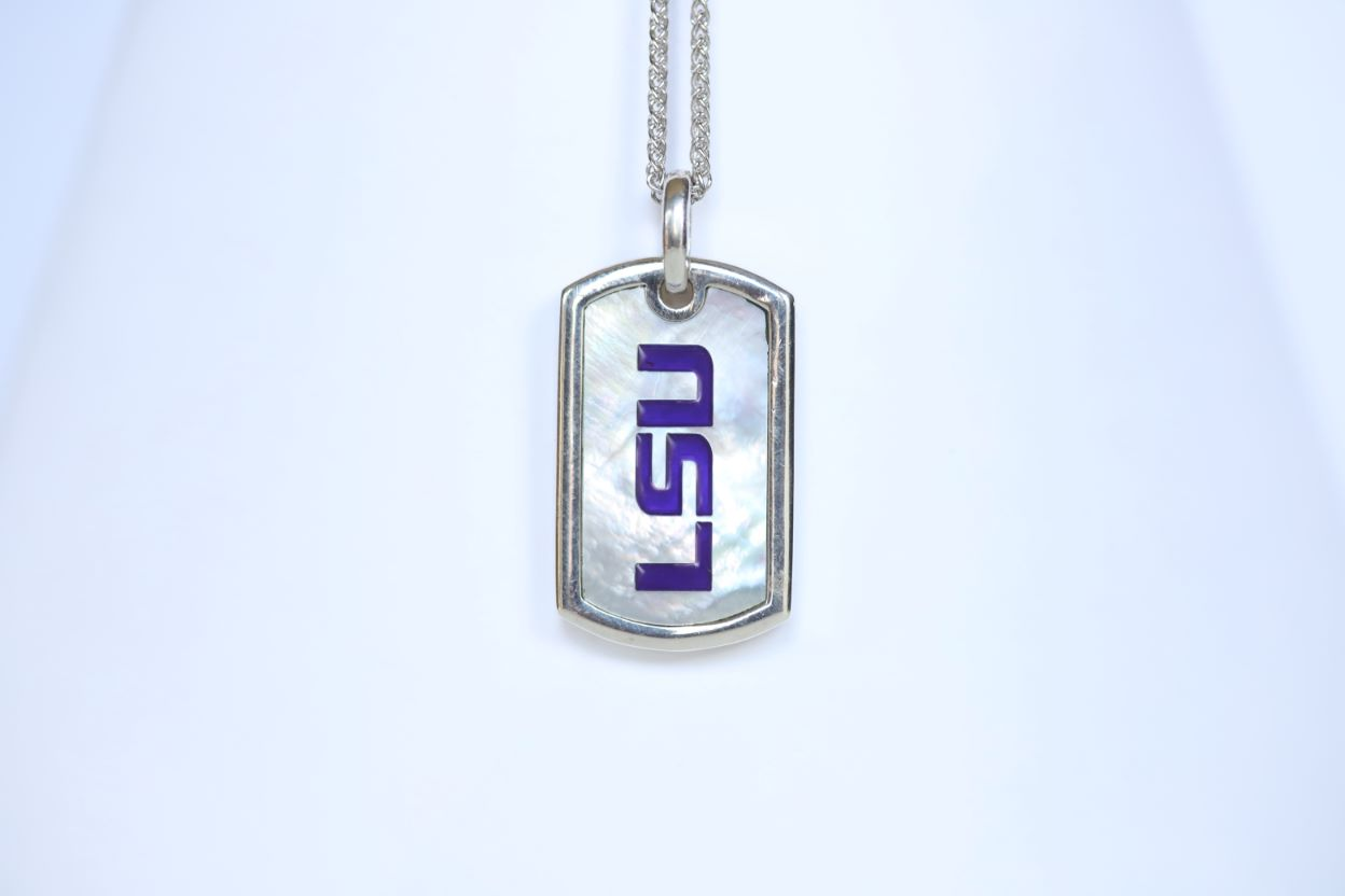 This piece is perfect for men or women! Each Mother of Pearl is one-of-a-kind. Features: Sterling silver Mother of pearl with purple enamel inlay Lobster clasp Pendant: 29x17mm LSU Loisianna State University