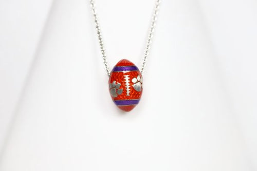 Support the Clemson Tigers with our orange enamel football pendant!   Features:  Sterling silver Purple and yellow enamel Lobster clasp Officially licensed product Pendant box included football baseball basketball college world series womens mens gift present mothers day fathers day clemson university clemson tigers clemson football team orange and purple  paw print