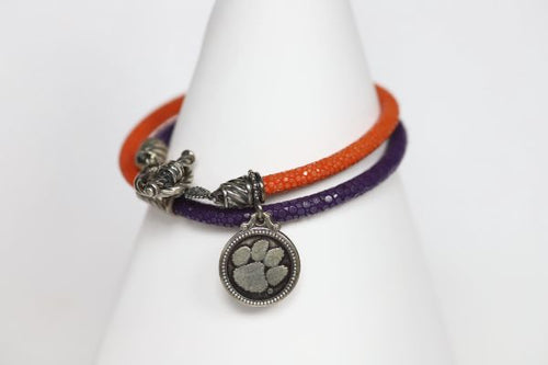Finish off your Clemson game day look with our purple and orange stingray leather charm bracelet.   Features:  Sterling silver Toggle clasp Stingray leather  Double sided charm Officially licensed product