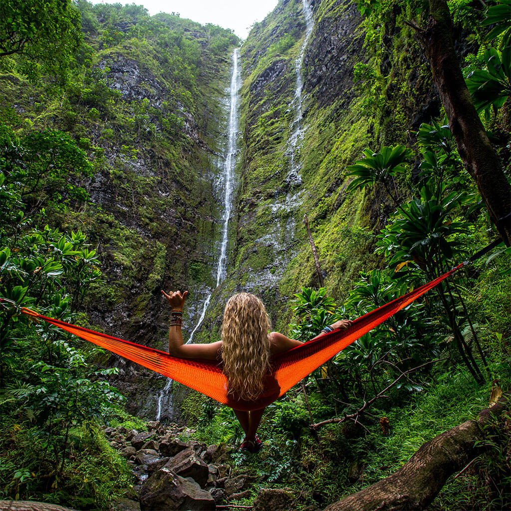 girl sitting in hammock looking at waterfall