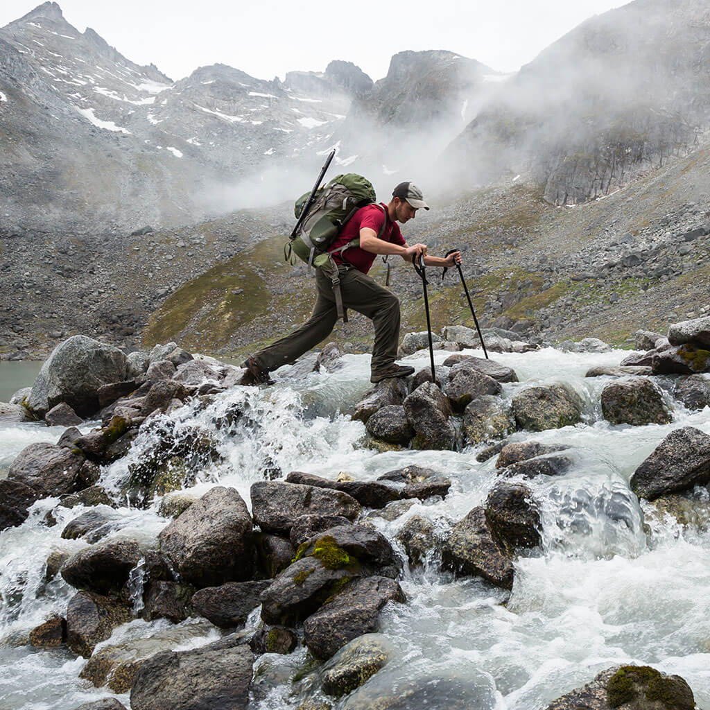 Man crossing rocky mountain river with trekking poles