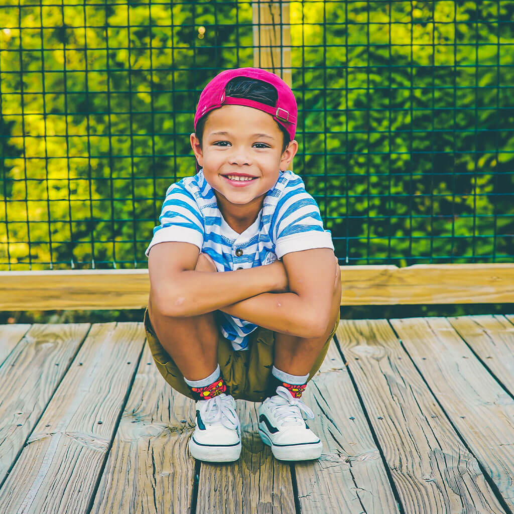 young boy on wooden bridge by railing