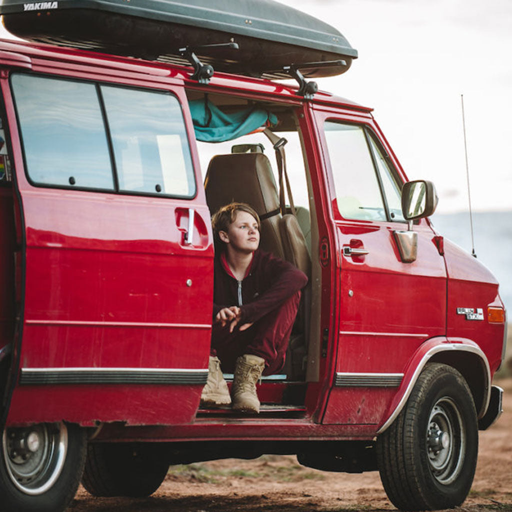 boy sitting in red camper van with door open gazing outside