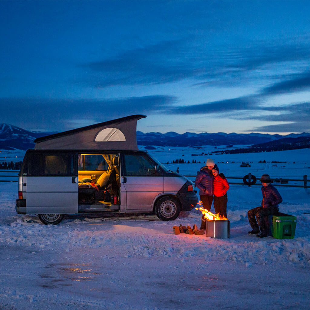 people standing around campfire during winter with camper van in background