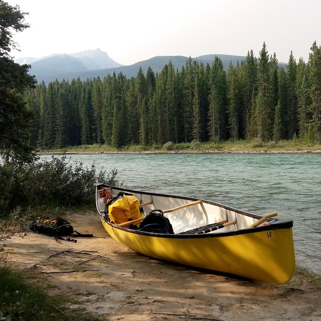Yellow canoe sitting on forest riverbank.