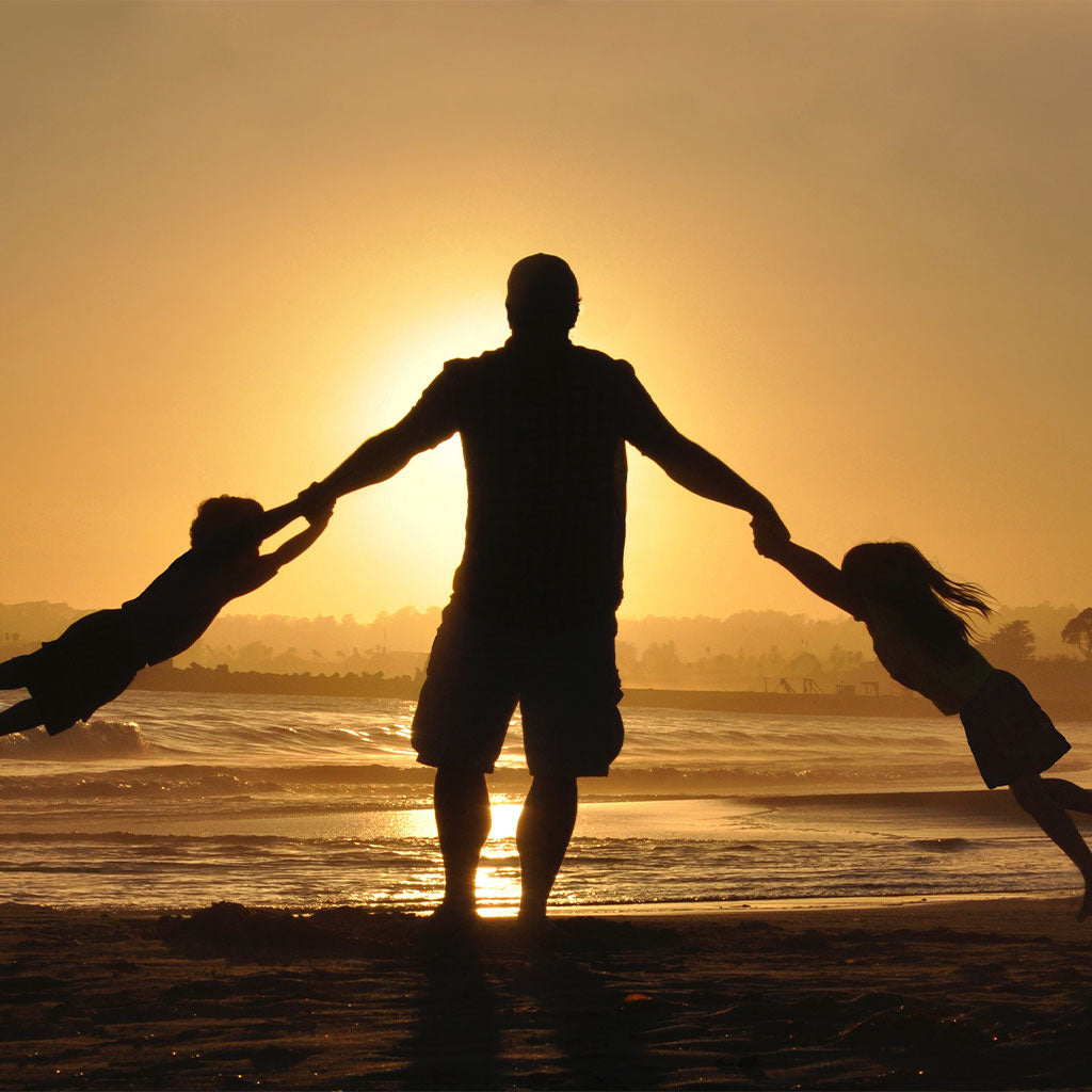 silhouette of dad swinging kids by arms on beach at sunset