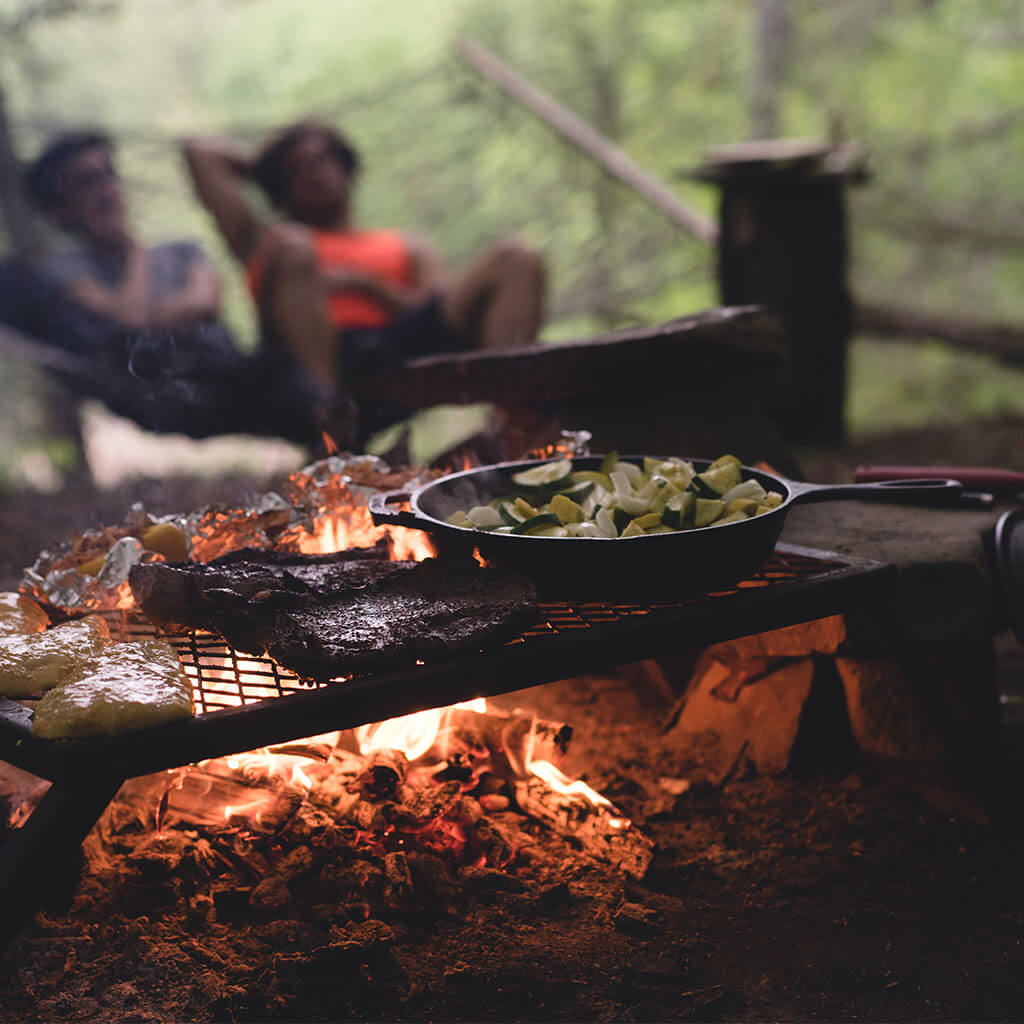 dinner being cooked over a campfire