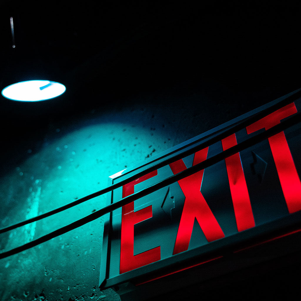 exit sign on wall with light shining down on it