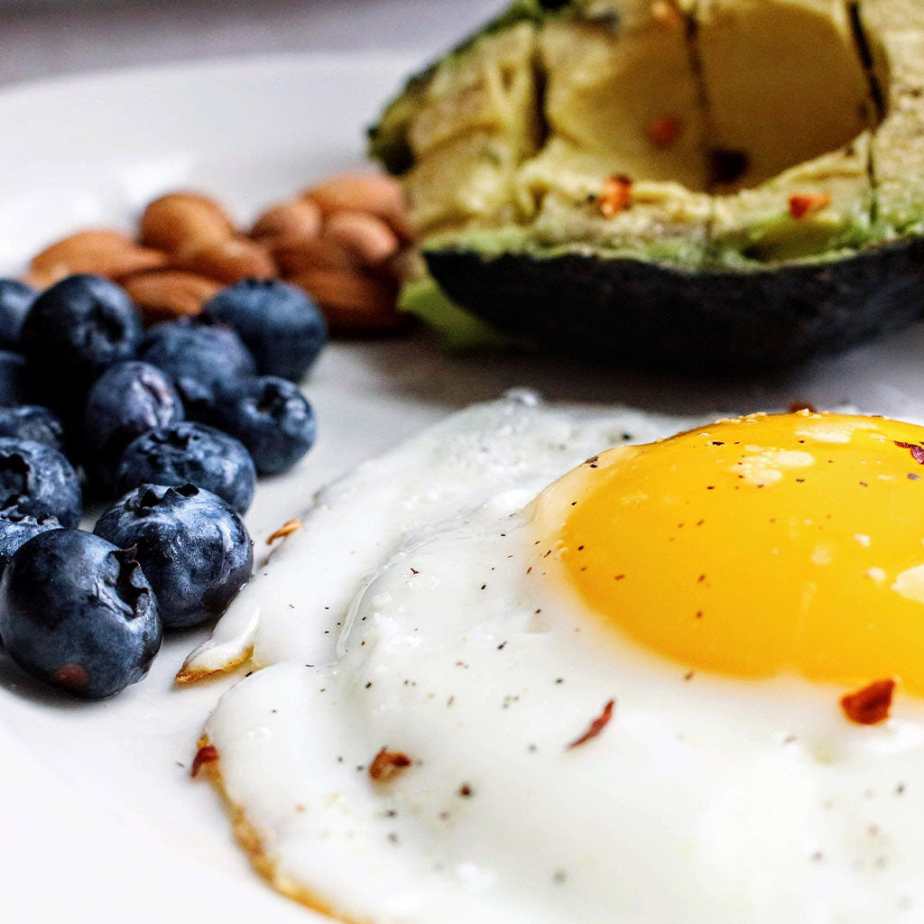 fried egg, blueberries, avocado and nuts and white plate