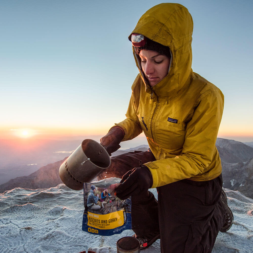 mountain climber pouring water in mountain house breakfast pouch on top of mountain