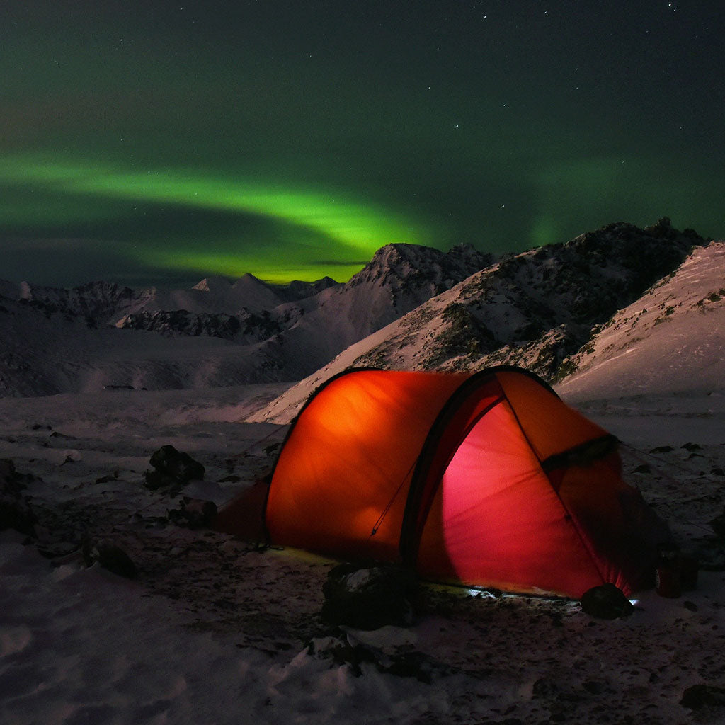 glowing red tent with the aurora in the background