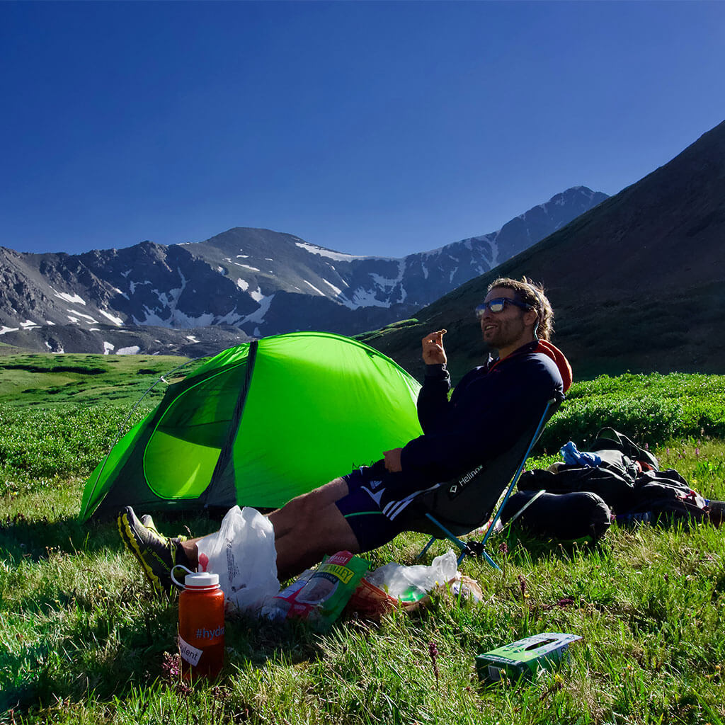 backpacker sitting in chair next to green tent