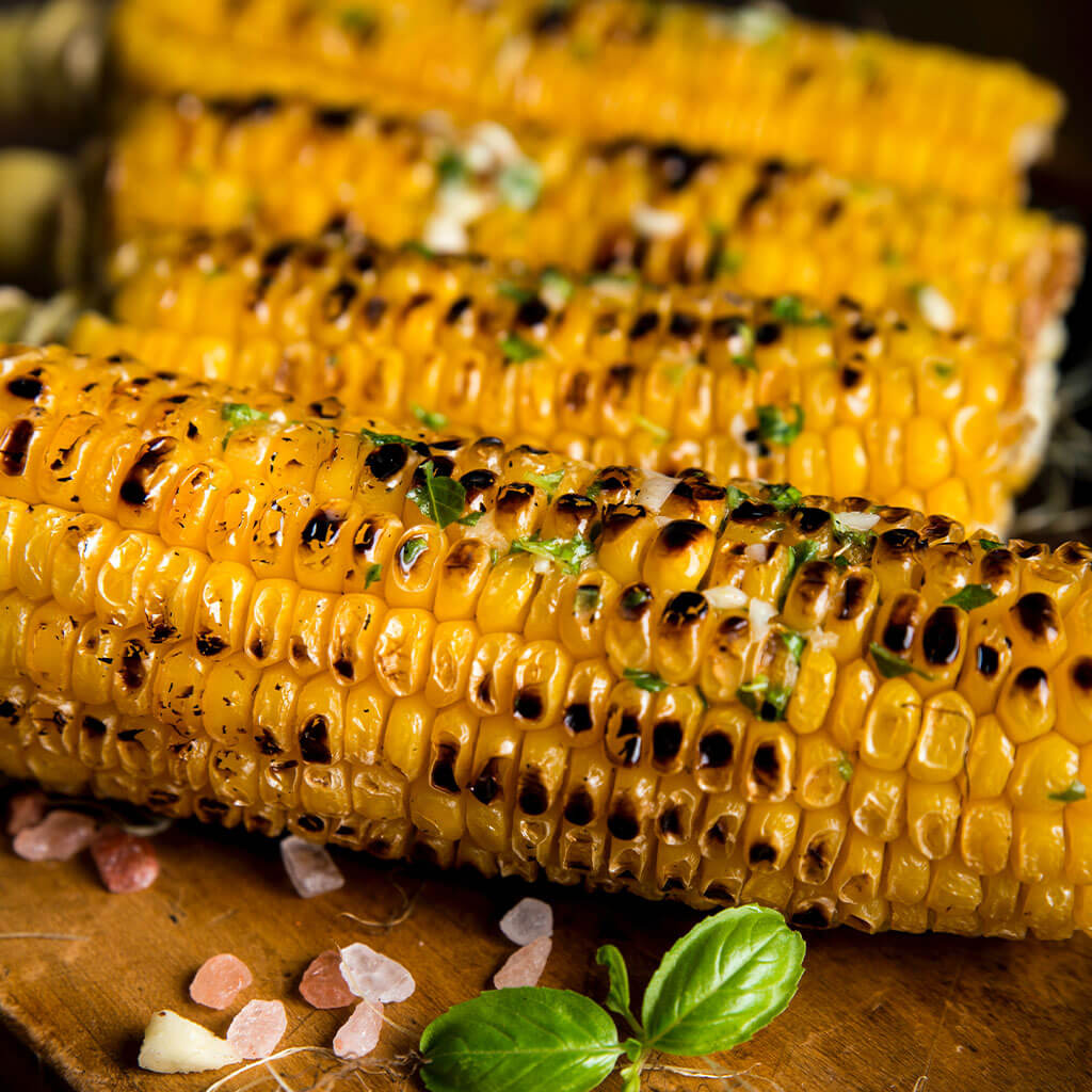 four pieces of grilled corn
