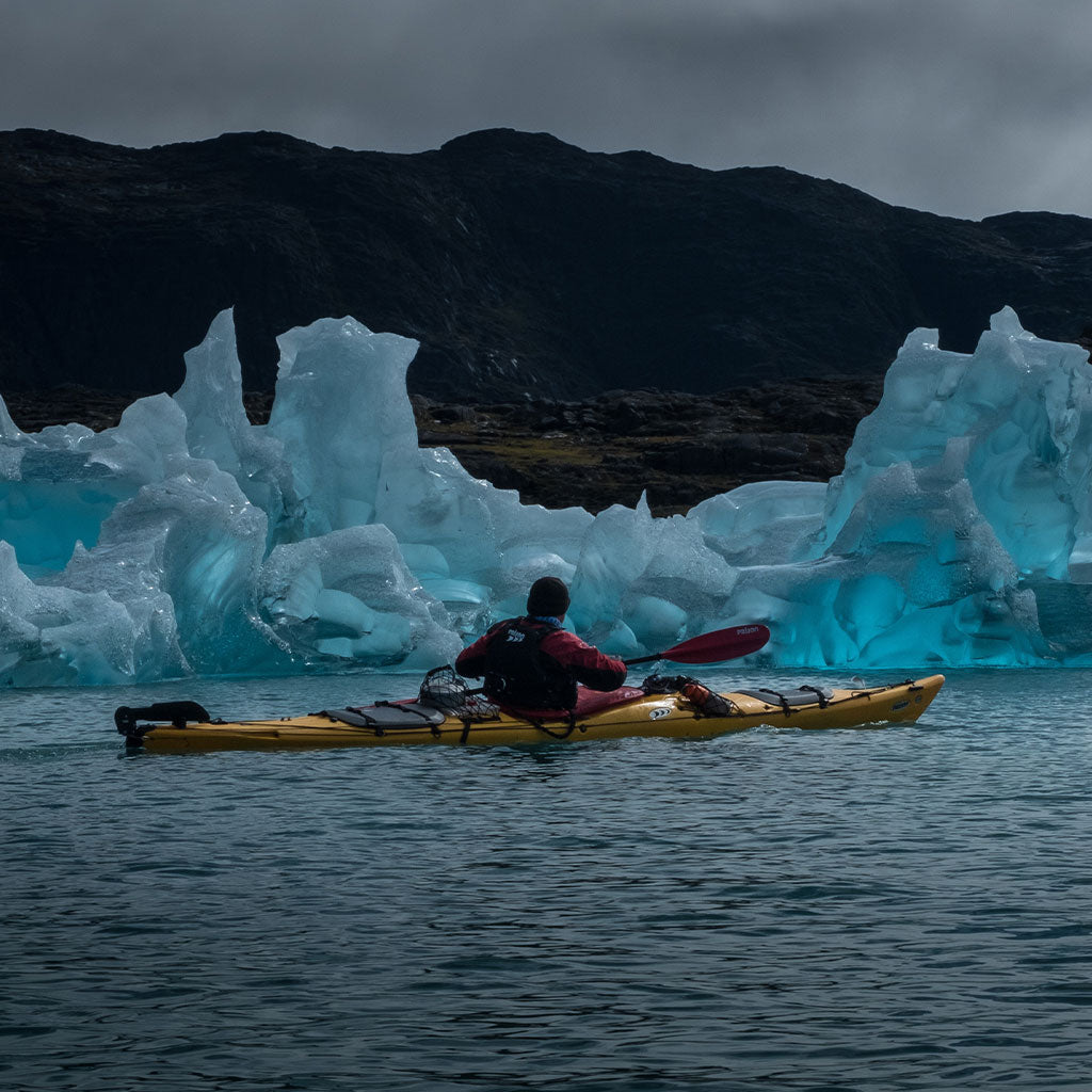person kayaking in front of glacier
