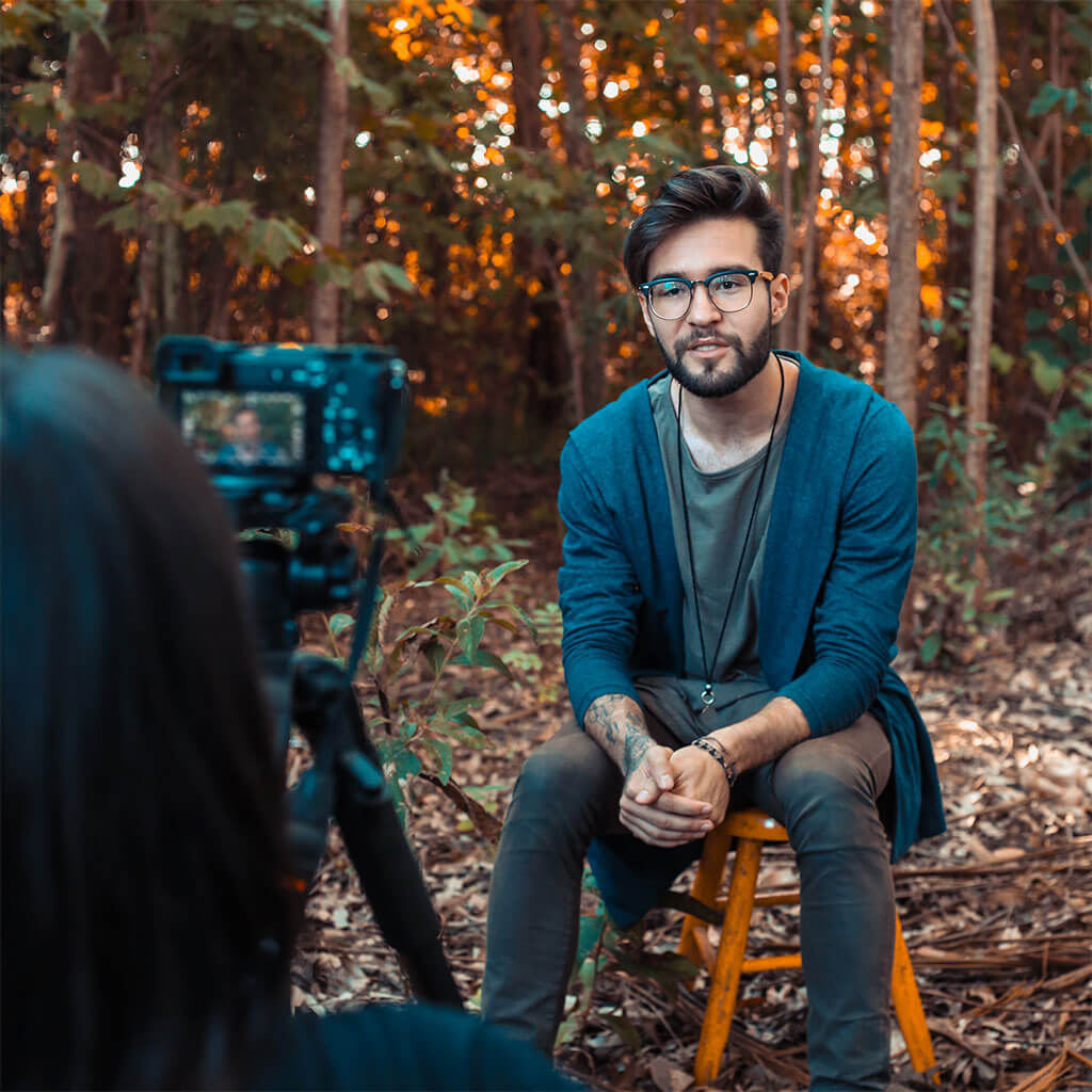 man sitting on stool in woods being filmed