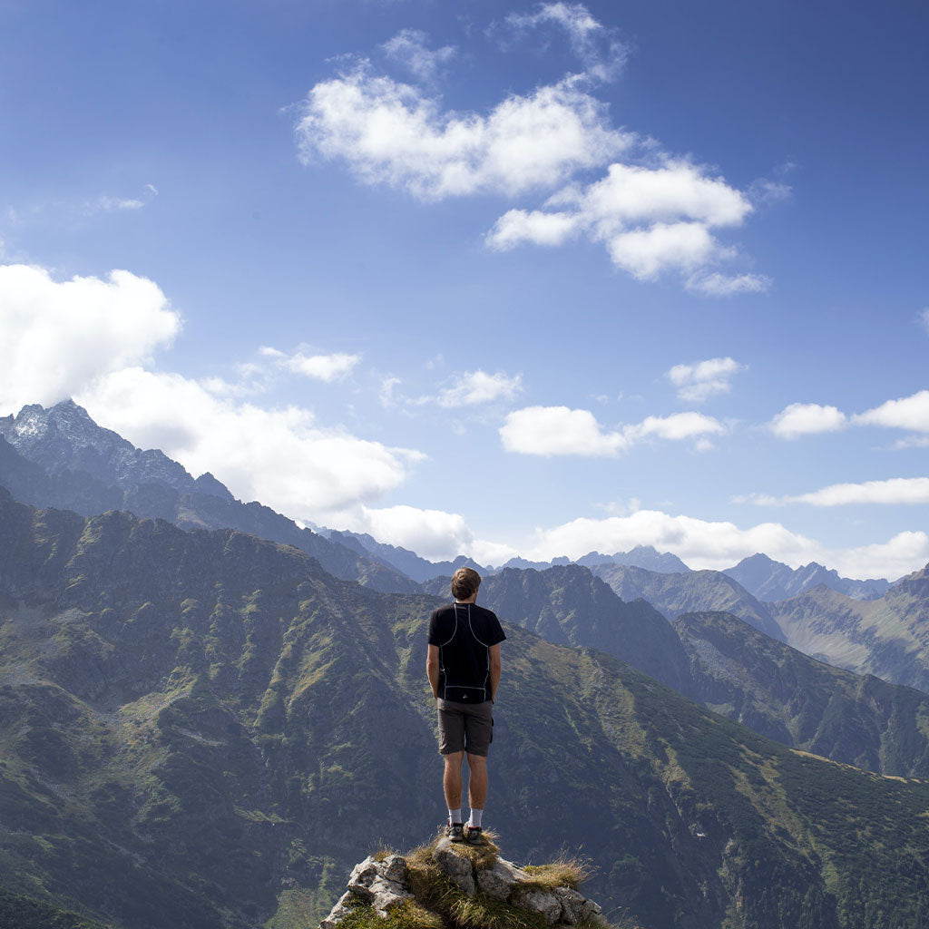 person standing on rock looking out at mountain range