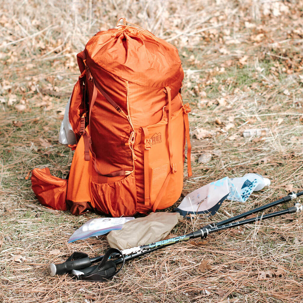 orange rei backpack and trekking poles on ground