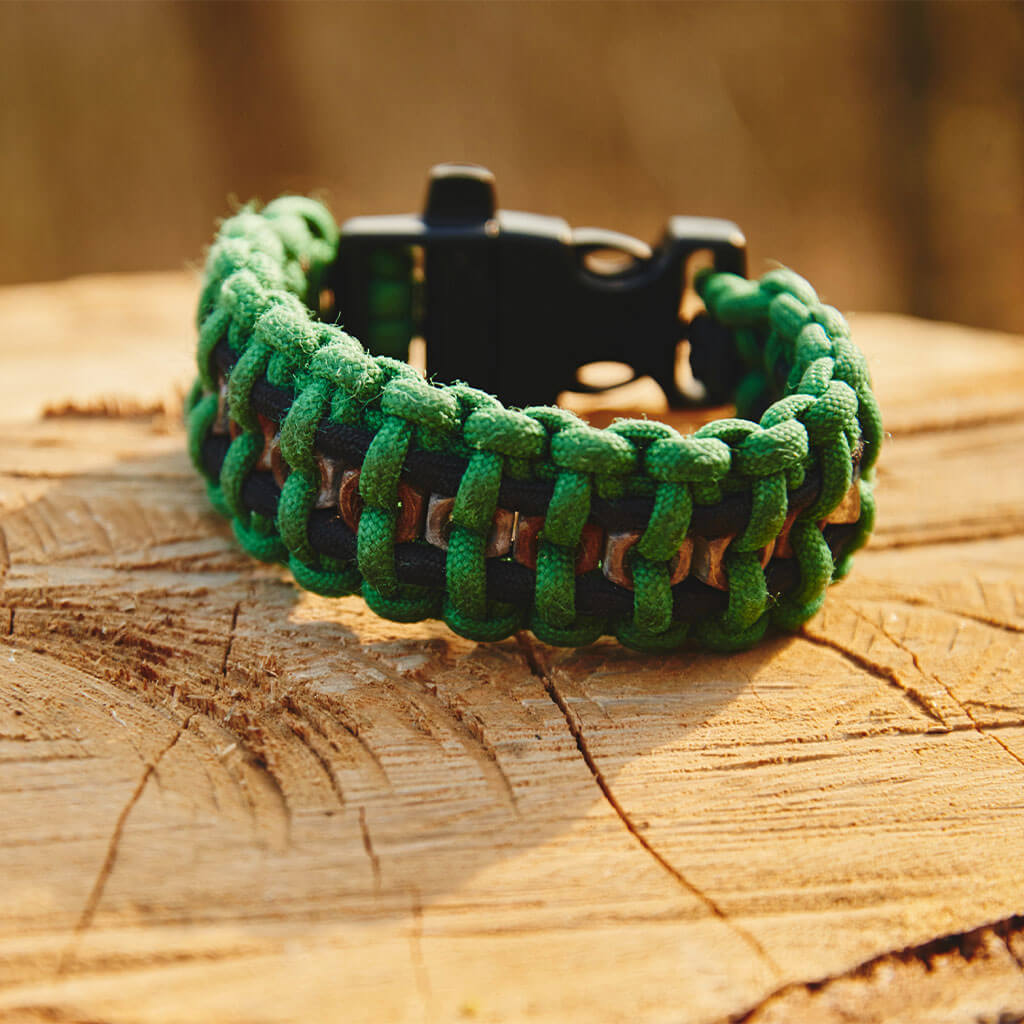 Green paracord bracelet on stump.