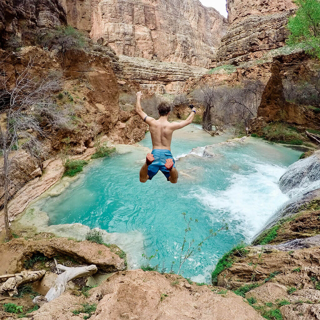 man cliff jumping into blue water