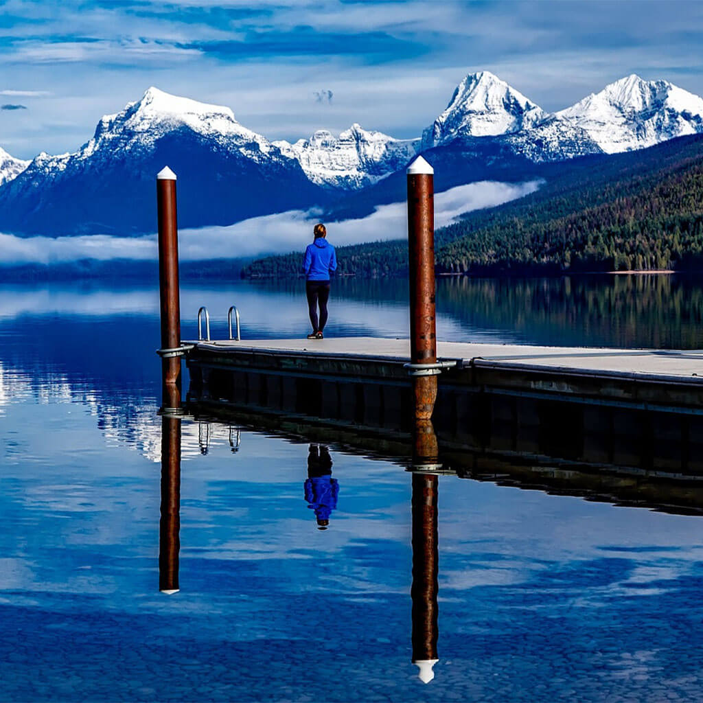 person standing on dock looking out at water and snow covered mountains
