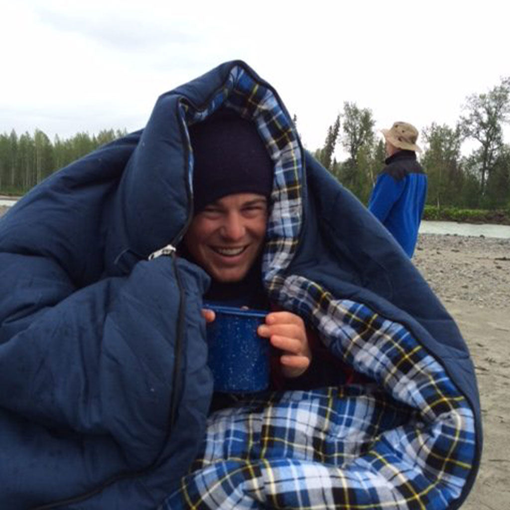 Rescued Kayaker, Dylan, Asbury, holding warm tin cup while wrapped in blue and plaid sleeping blanket on river bank