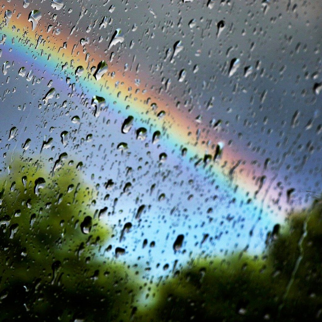 Rainbow from behind wet window.