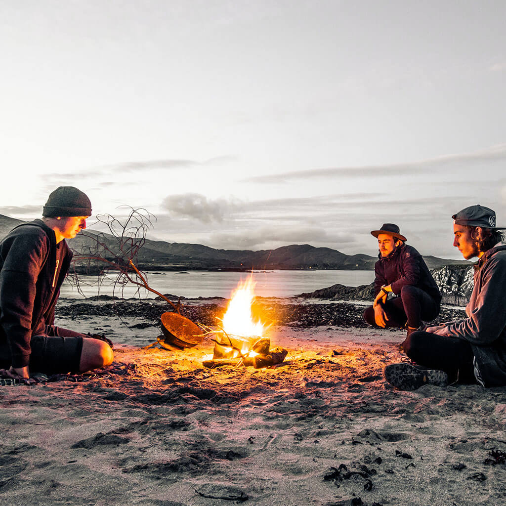 three guys sitting around campfire