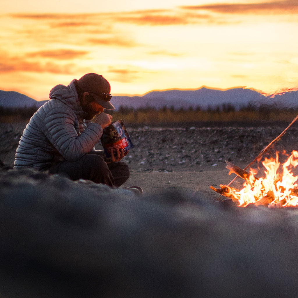guy eating from mountain house freeze dried food pouch by campfire at dusk