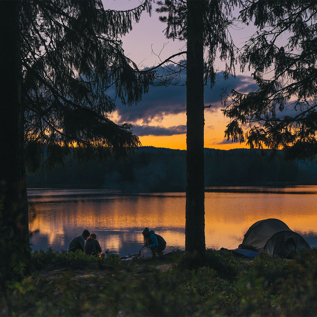 Three people camping by lake at sunset