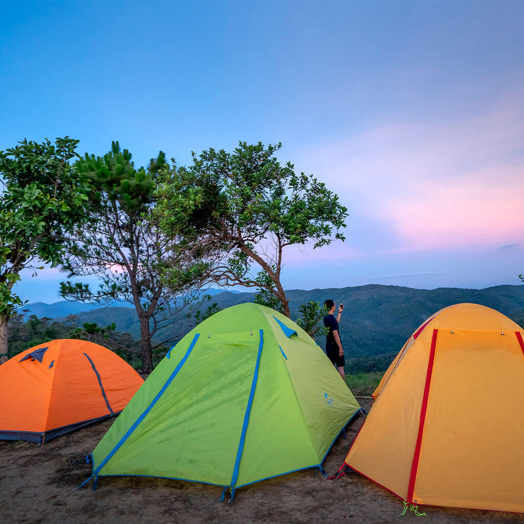 three tents atop a mountain peak with person looking at mountain view