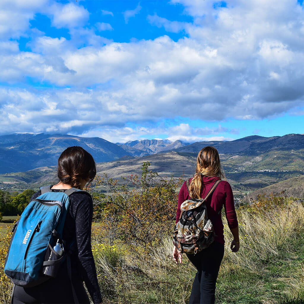two girls hiking down mountain trail
