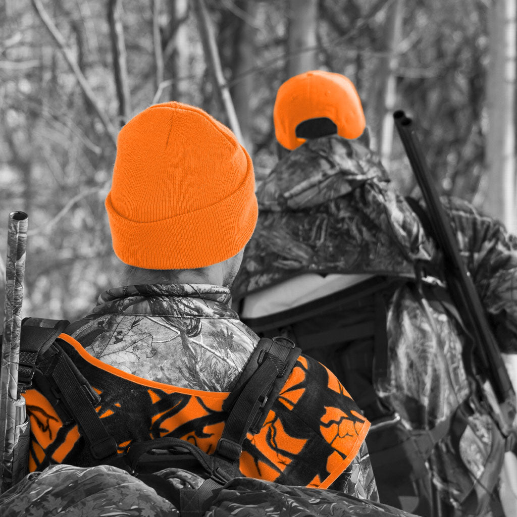 two hunters walking through woods wearing blaze orange