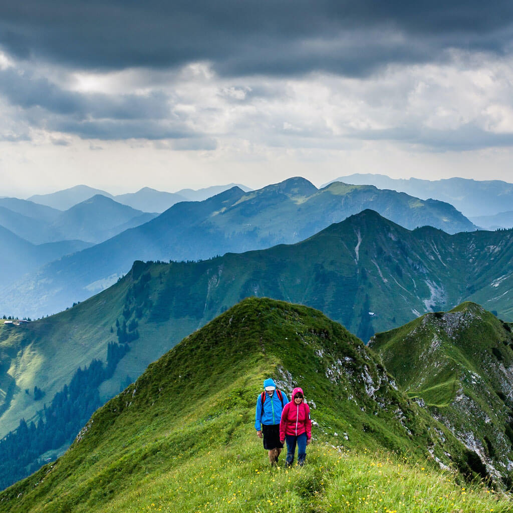 Two people hiking grassy mountain ridge