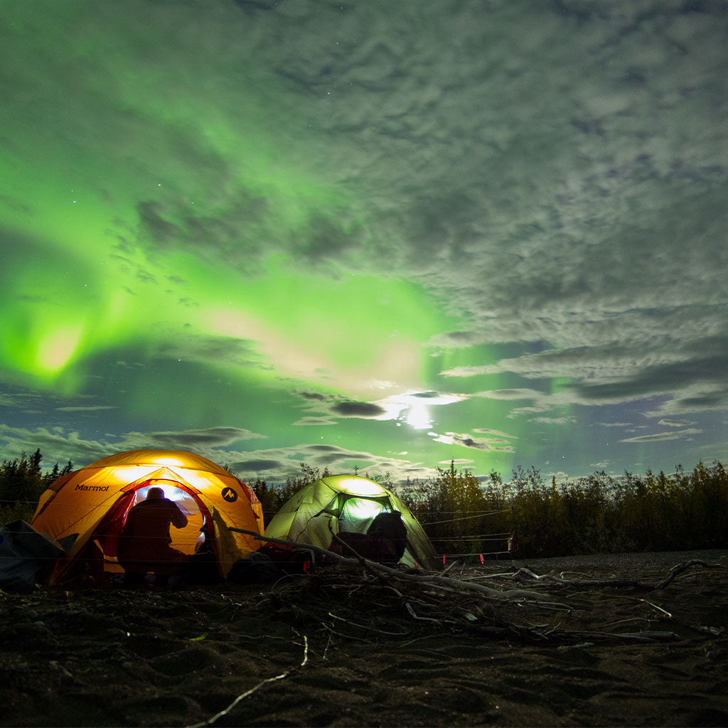 Two tents set up underneath northern lights during winter