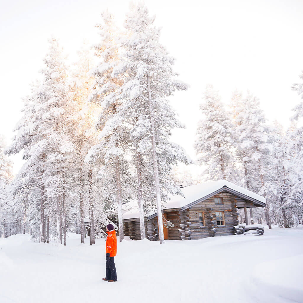 person standing in snow outside cabin while daylight